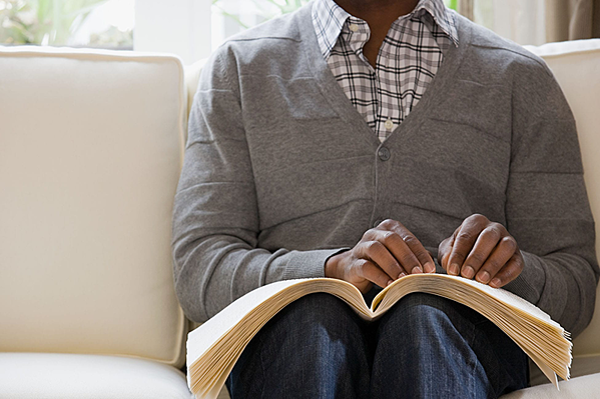 Personne assise sur un canapé en train de lire un livre