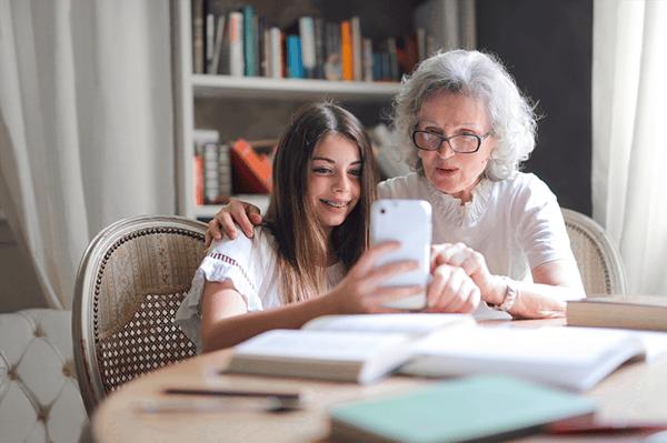 Petite fille qui montre quelque chose sur son téléphone à sa grand-mère