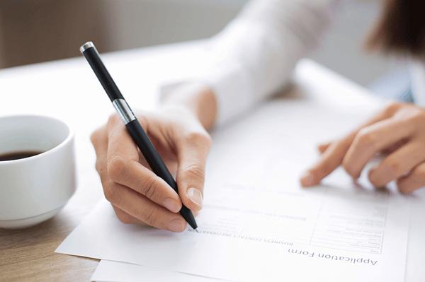 Personne en train de compléter un dossier administratif avec son stylo